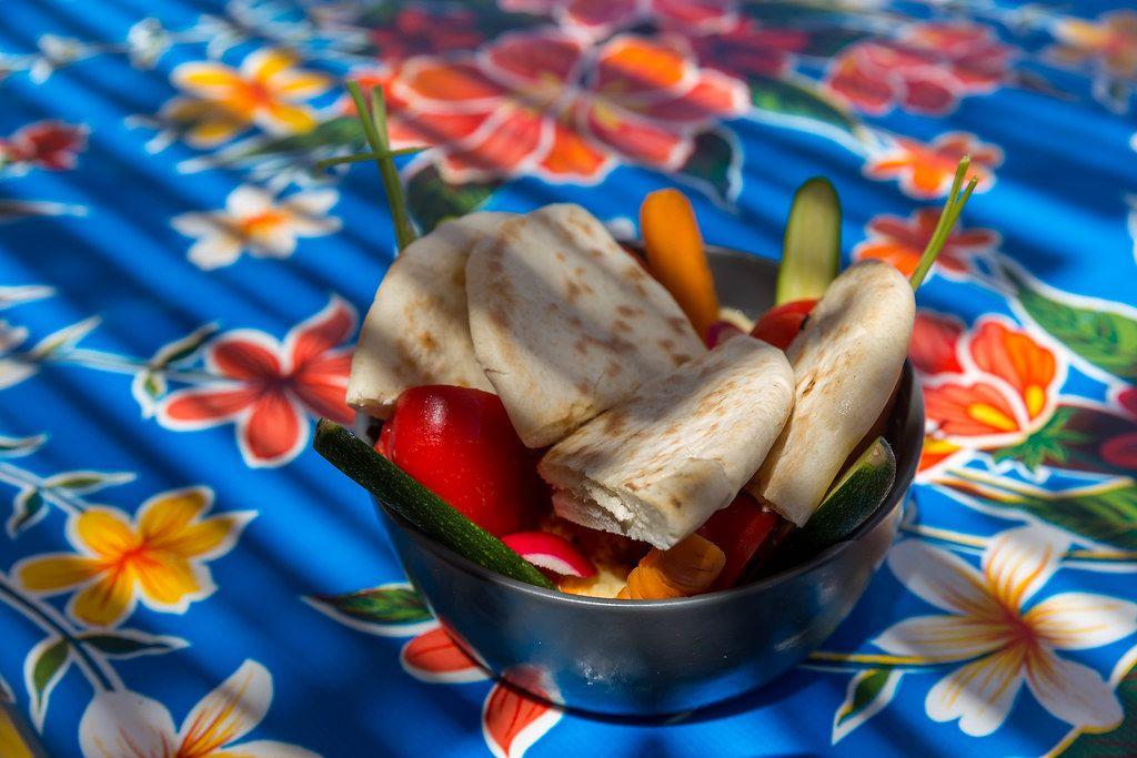 Schüssel mit Hummus, geschnittenem Gemüse und Pita auf Tischdecke mit Blumen-Muster