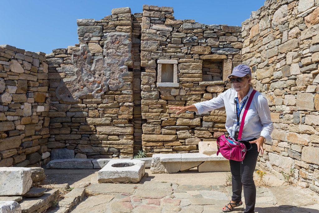 Schutz vor Corona: Reiseleiterin auf Delos trägt transparentes Visier, das Mund und Nase bedeckt