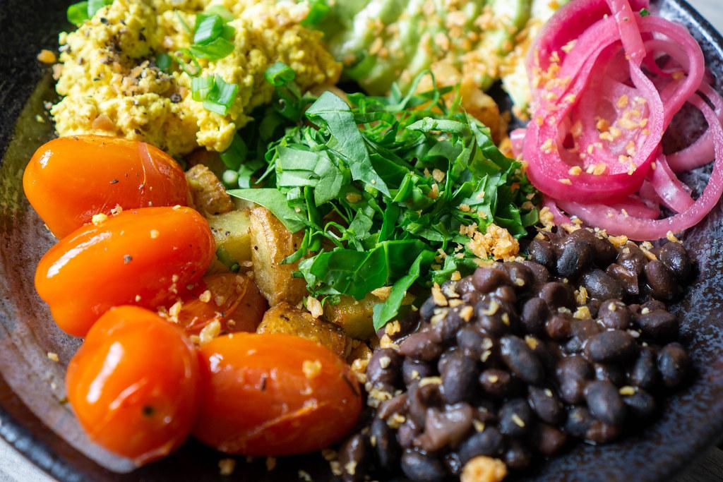 Schwarze Bohnen, Kirschtomaten, Rührei, Bratkartoffeln und Kräuter auf einem Teller als gesunde Mahlzeit Nahaufnahme
