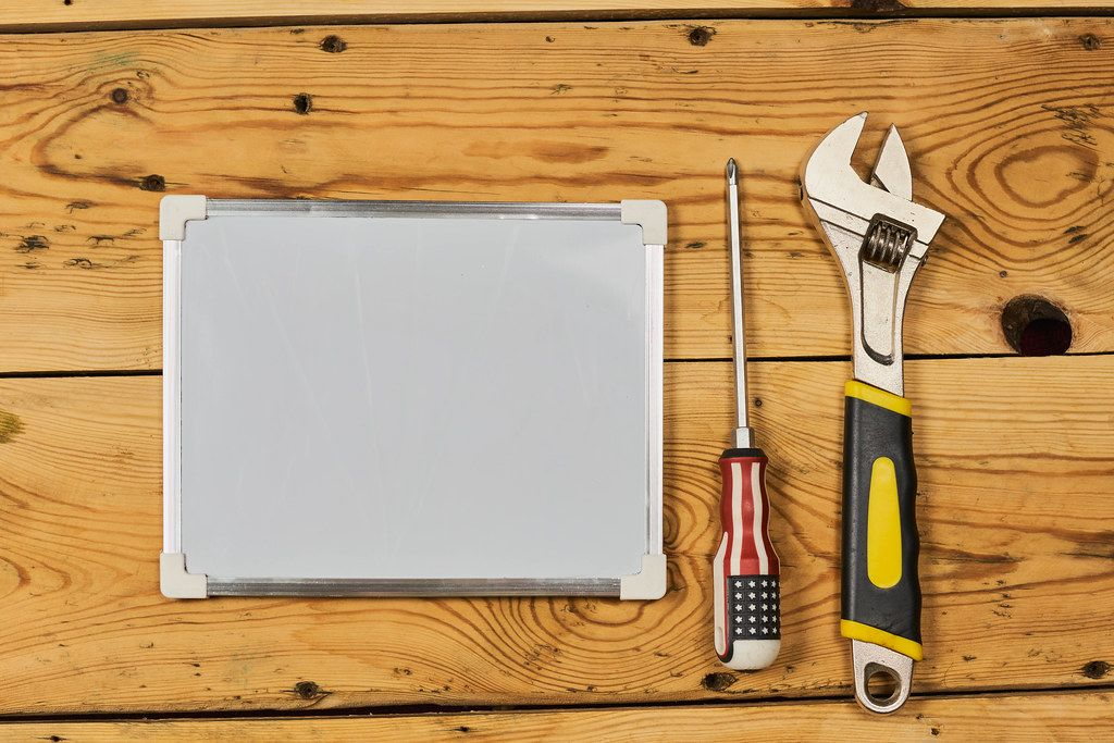 Screwdriver, adjustable wrench and whiteboard with copy space on the wood