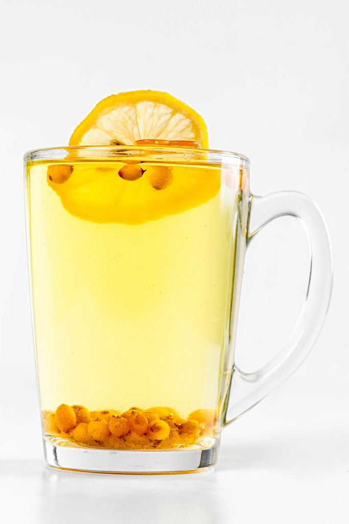 Sea buckthorn tea in a glass cup on a white background