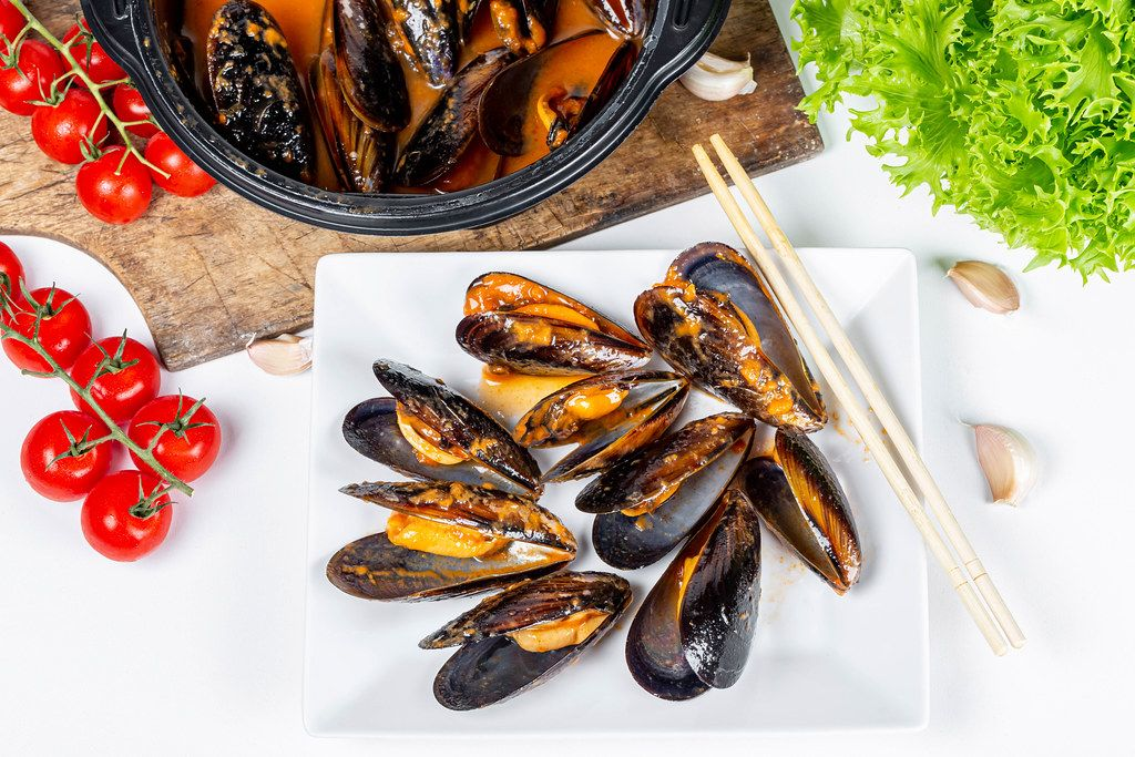 Sea food, delicious mussels with spicy sauce on a white background with vegetables, top view