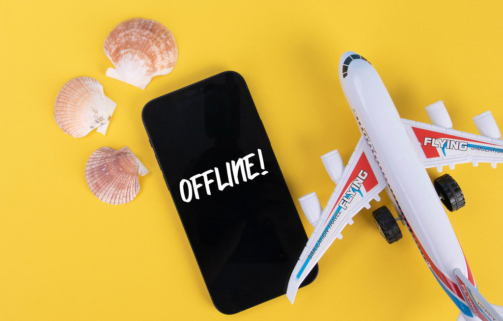 Sea shells, airplane and smartphone with Offline text