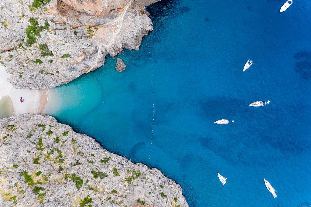 Sechs Boote im blauen Wasser bei der Bucht von Sa Calobra  auf Mallorca. Overhead-Luftaufnahme