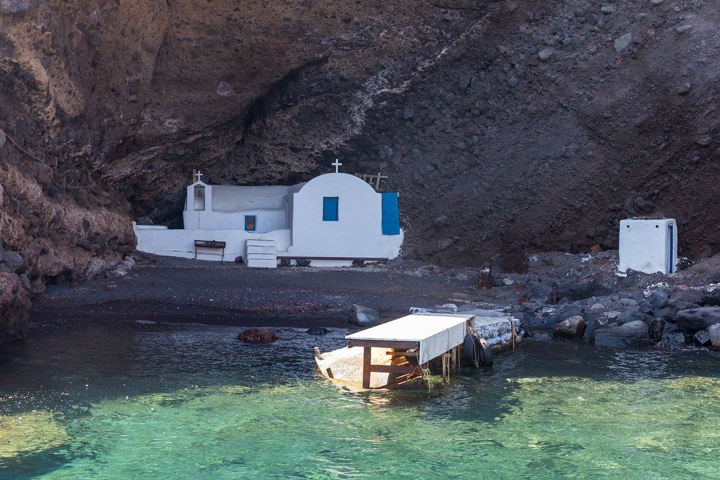 Secret gems: a small white church with blue doors hidden on a beach only reachable by boat