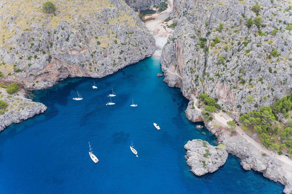 Segel- und Motorboote im blauen Wasser vor der Steilküste bei Sa Calobra auf Mallorca. Luftbild