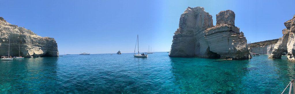 Segelboote zwischen Felsformationen auf dem blauen Kretischen Meer in der Bucht von Milos, Griechenland
