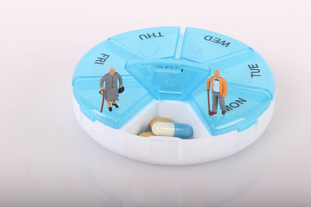 Senior couple standing on pill reminder box
