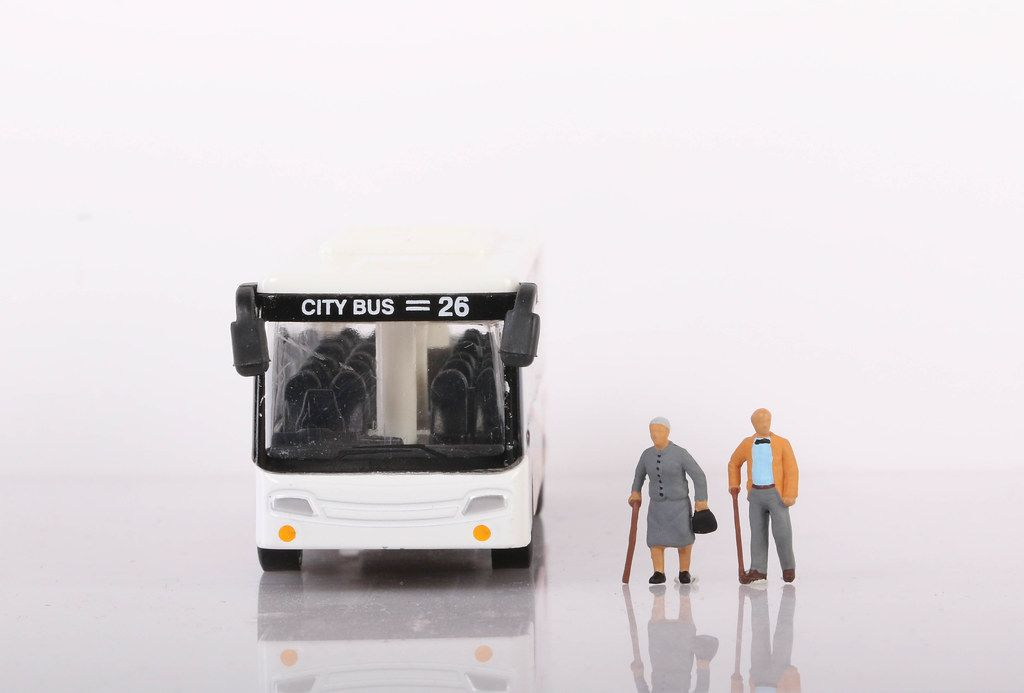 Senior couple with bus on white background