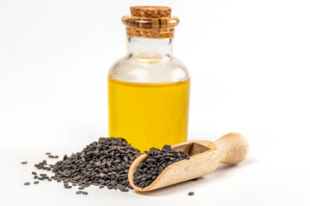 Sesame oil in glass bottle with black sesame seed in wooden scoop on white