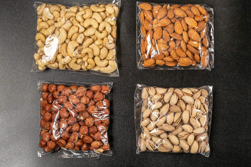 Set of cashew nuts, almonds, hazelnuts and pistachios on a black background