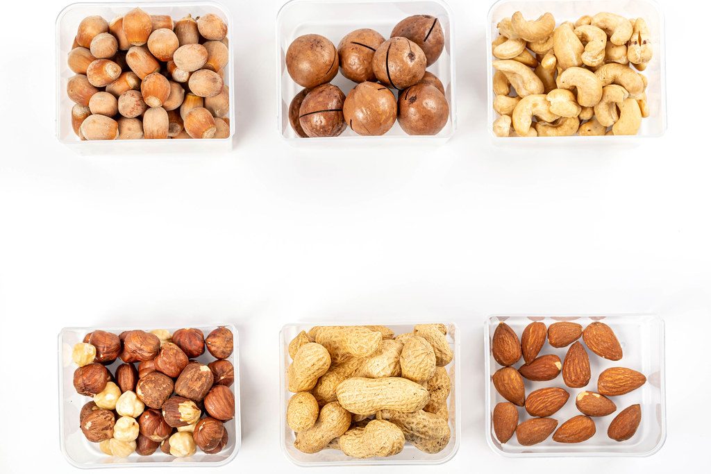 Set of different nuts in plastic boxes on a white background with free space, top view
