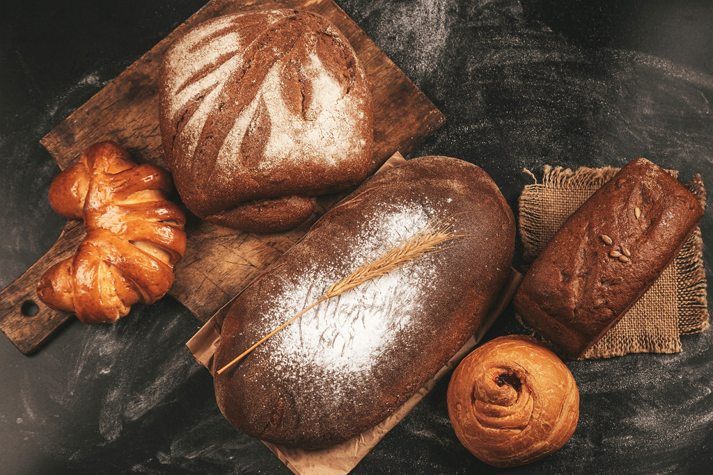 Set of rye bread and buns on a dark background, top view