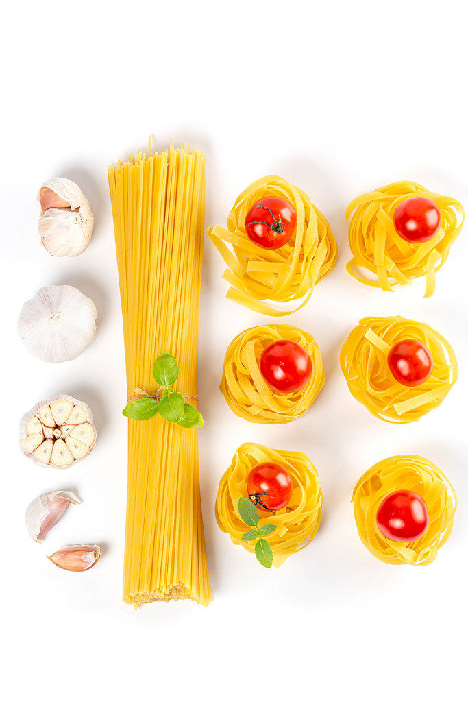 Set with spaghetti and fettuccine pasta, garlic, basil and tomatoes, top view