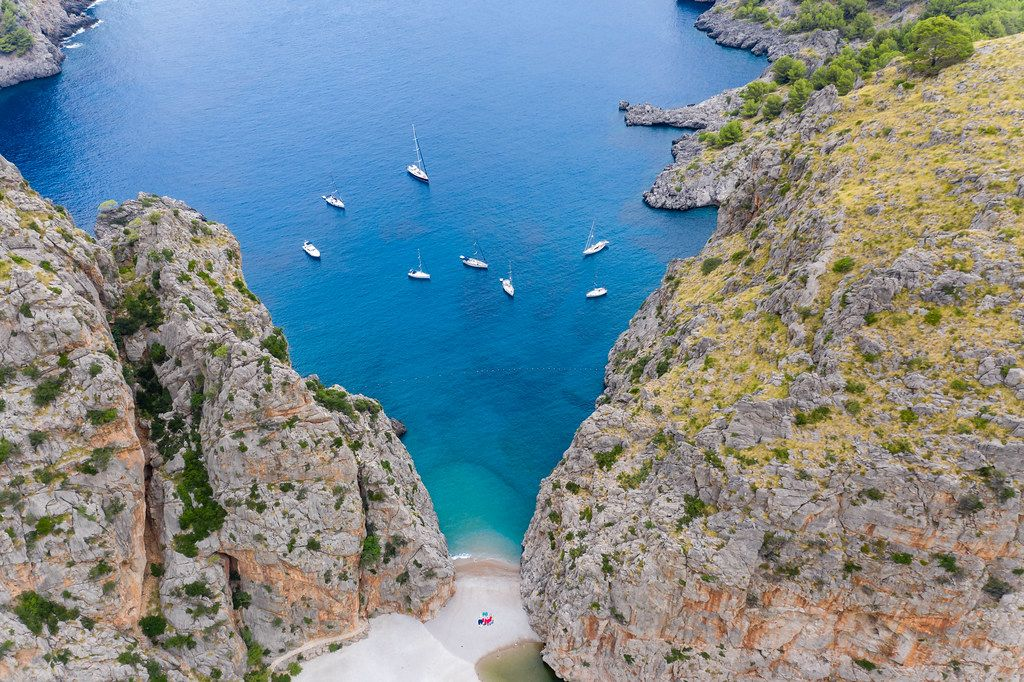 Seven sailboats and one motor boat in the bay of Sa Calobra on the northwest coast of Majorca, drone pic
