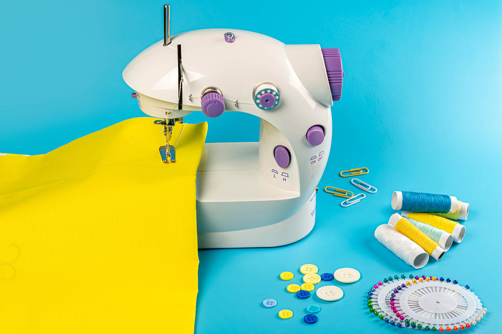 Sewing machine with yellow fabric on blue background
