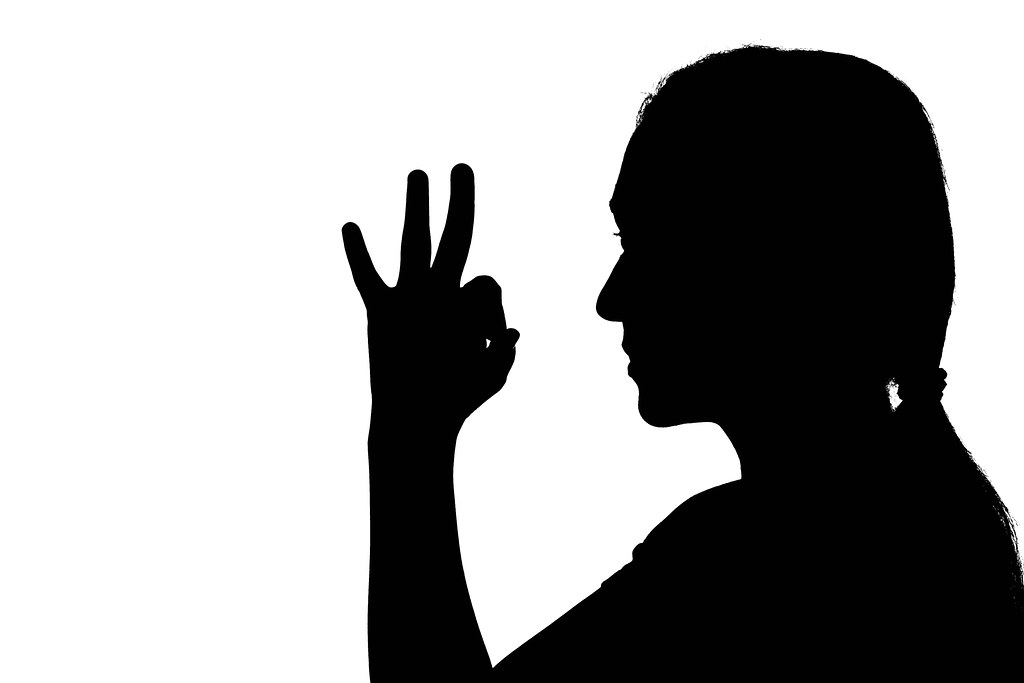 Shadow of a woman showing OK sign hand gesture