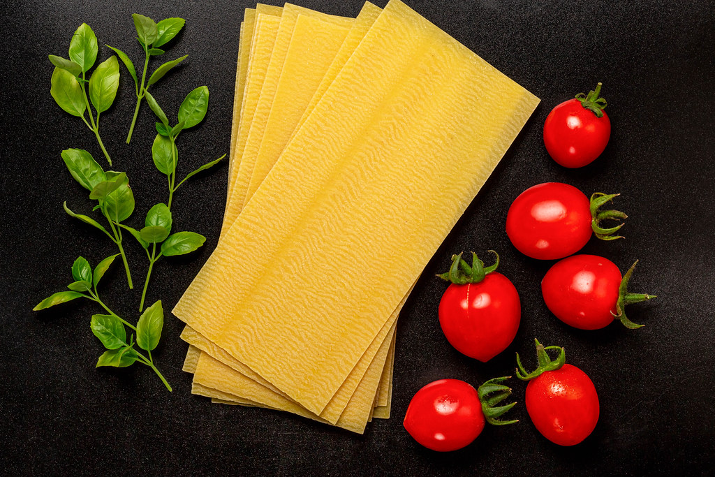 Sheets for lasagna with basil leaves and tomato on black, top view