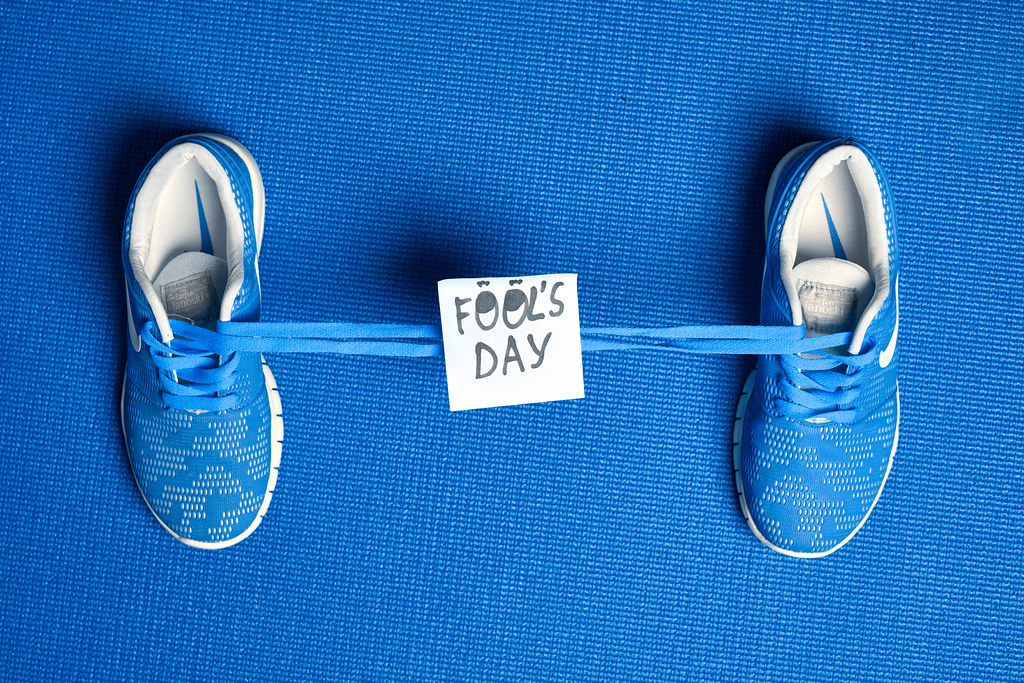 Shoes tied together and note with phrase - Fools day on blue background