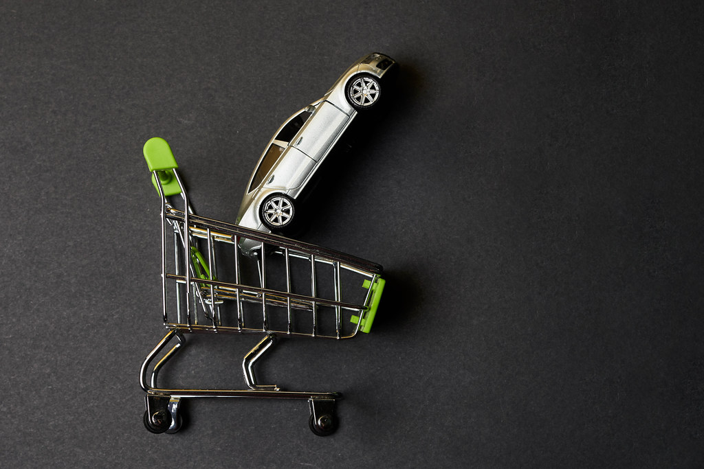 Shopping cart and toy car on dark background