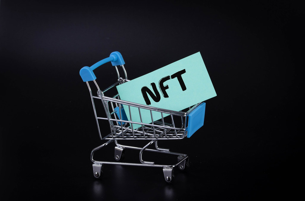 Shopping cart with a paper and NFT text on black background