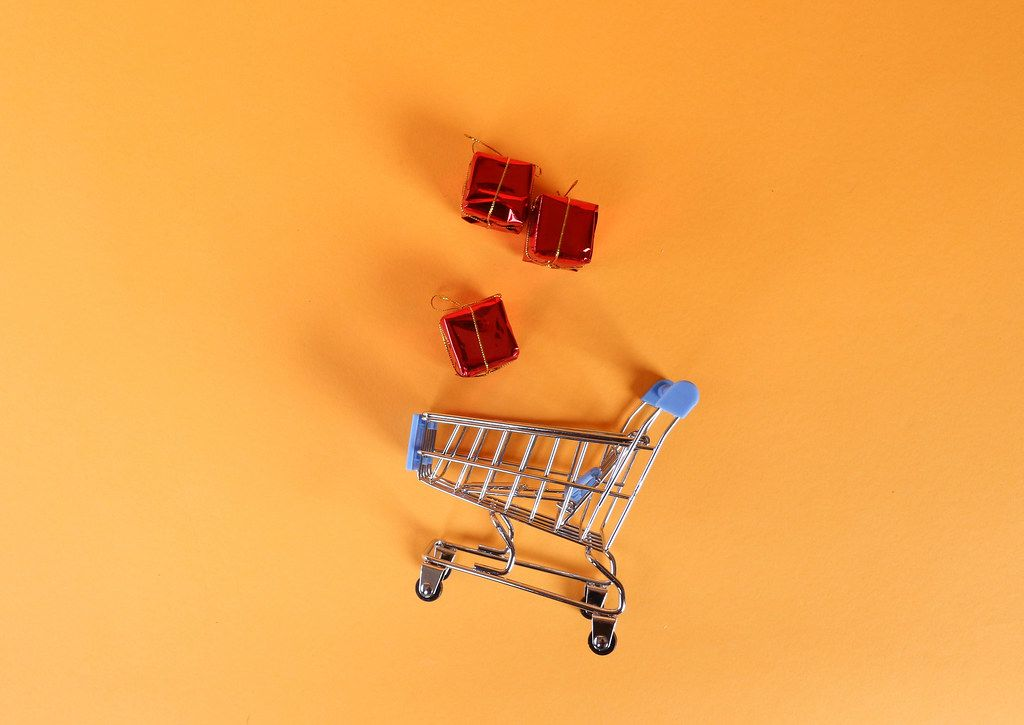 Shopping trolley with gifts on orange background