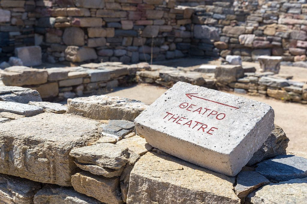 Sign on a stone pointing the way to the ancient theatre of Delos, written in English and Greek