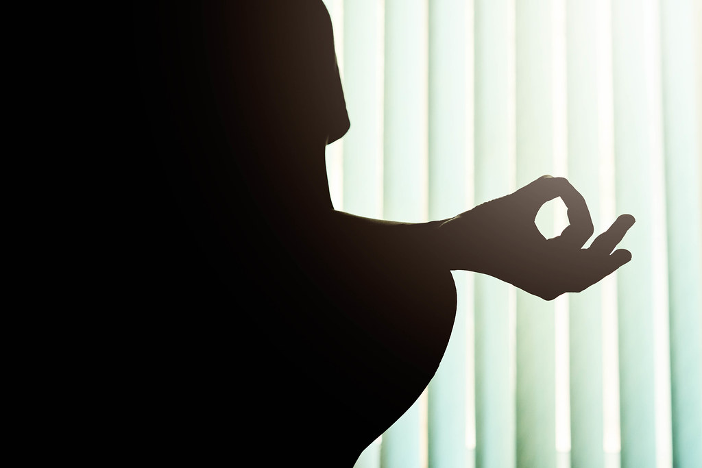 Silhouette of a young woman doing yoga - Gyana Mudra