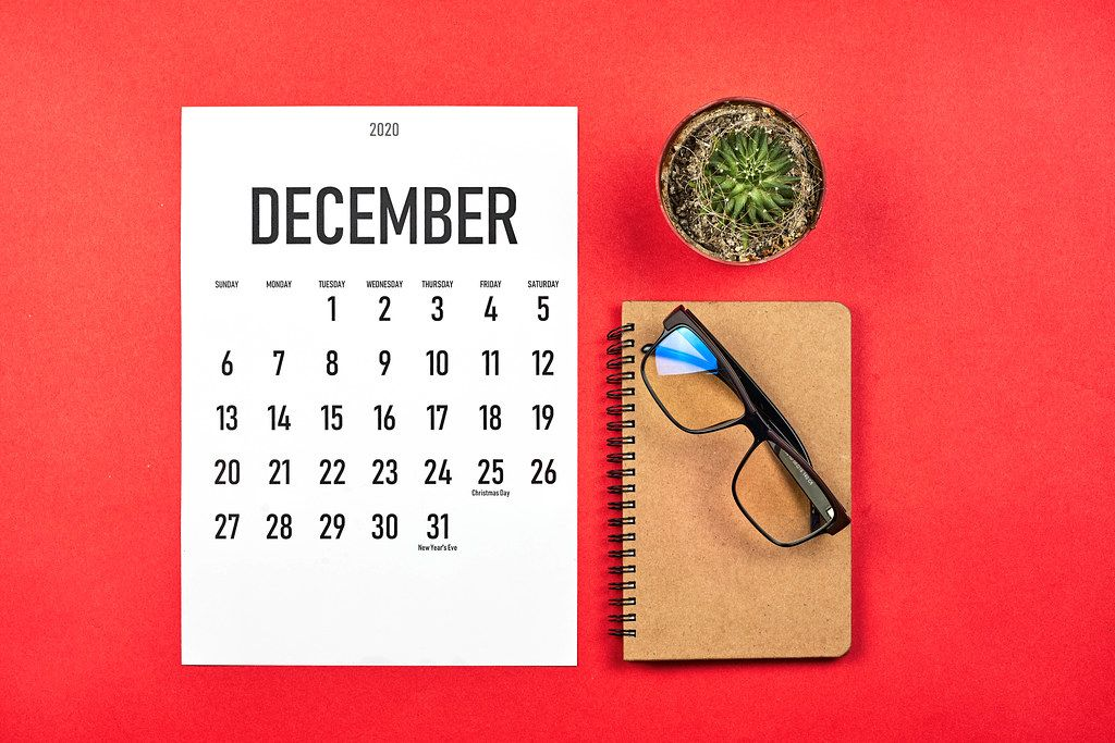 Simple December calendar at stylish red colored office desk