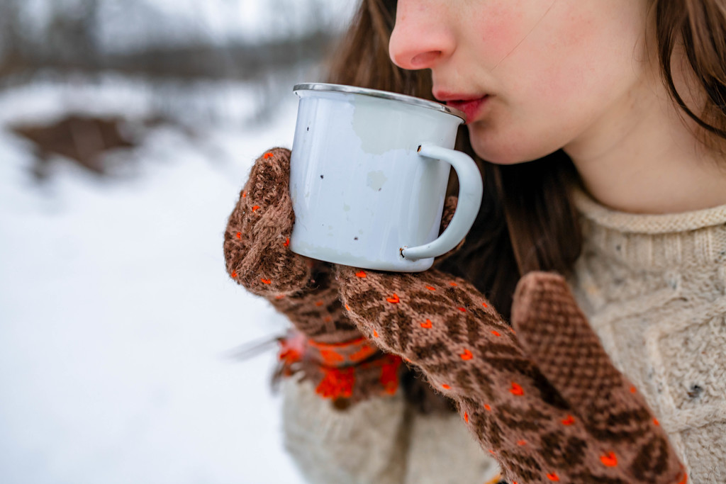 Sipping Tea On MEtal Cup Wintertime Outdoors