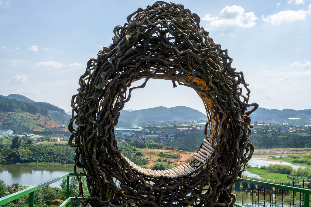 Sitz aus Baumwurzeln und Ästen für ein Fotoshooting mit Bergen und einem See im Hintergrund in Dalat, Vietnam