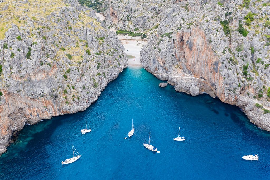 Six boats in the blue waters by the entrance of the bay of Sa Calobra. Bird's eye view in Mallorca