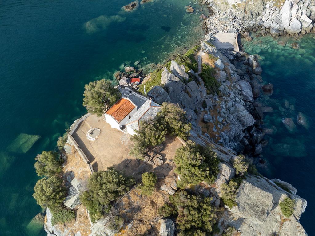 Skopelos: Drohnenaufnahme der Kapelle von Agios Ioannis auf einer vom Meer umgebenen Felsformation