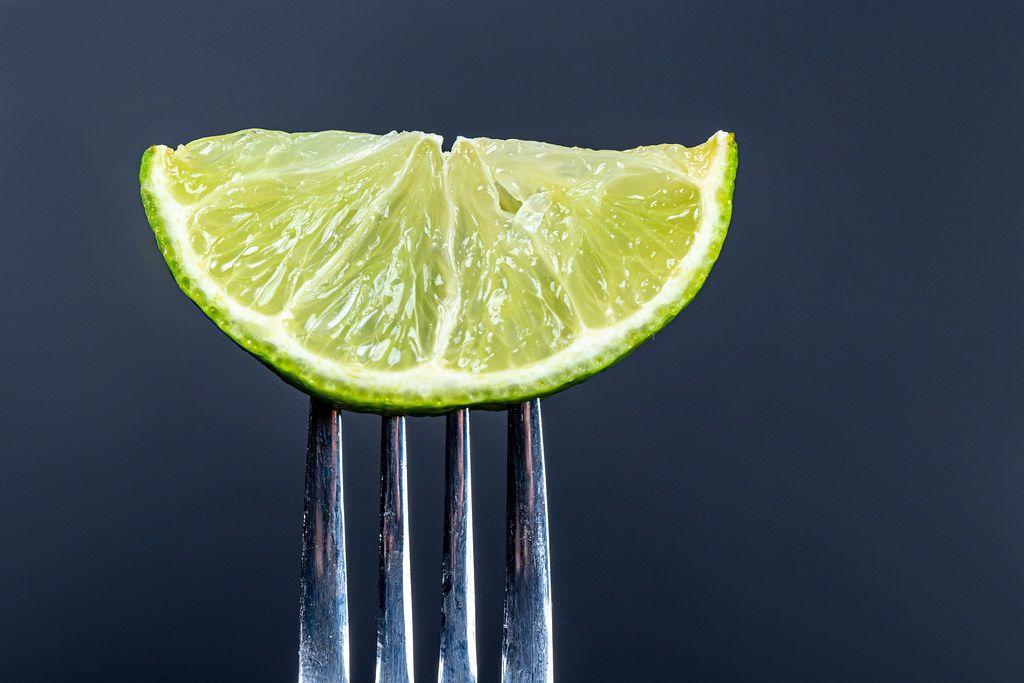 Slice of lime on a fork on a black background