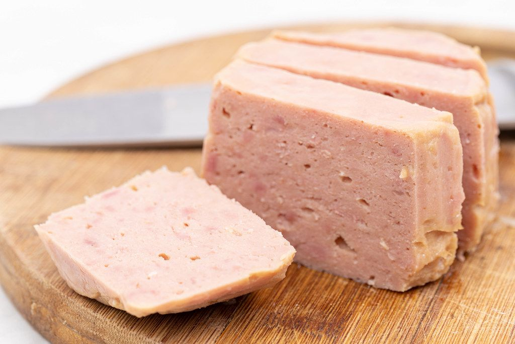 Sliced and served Luncheon Meat on the wooden cutting board