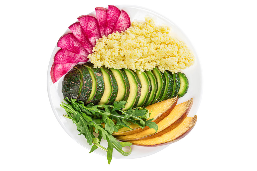Sliced avocado, mango, red radish, arugula leaves and couscous, healthy food concept