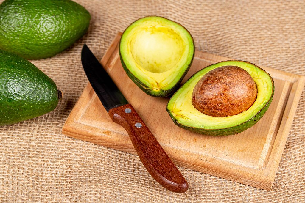 Sliced avocado with knife on wooden kitchen board with burlap
