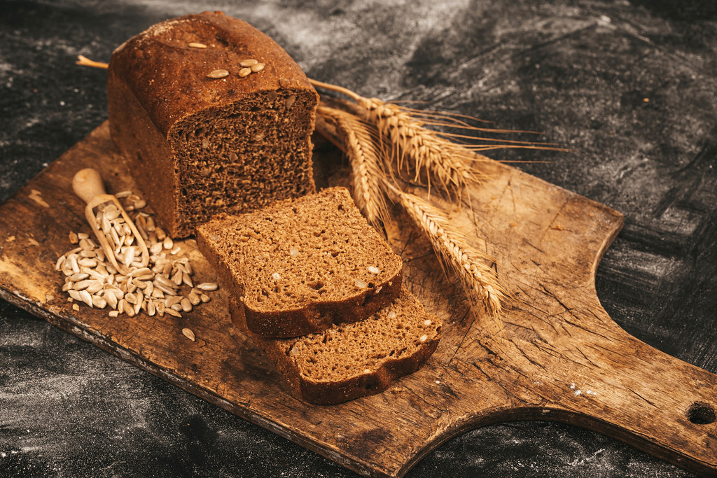 Sliced black bread with sunflower seeds and wheat ears on a dark background