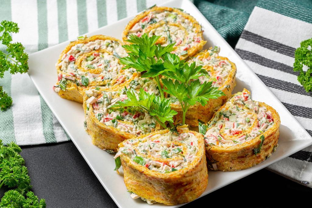 Sliced cheese omelette roll with herbs and crab sticks on a white plate