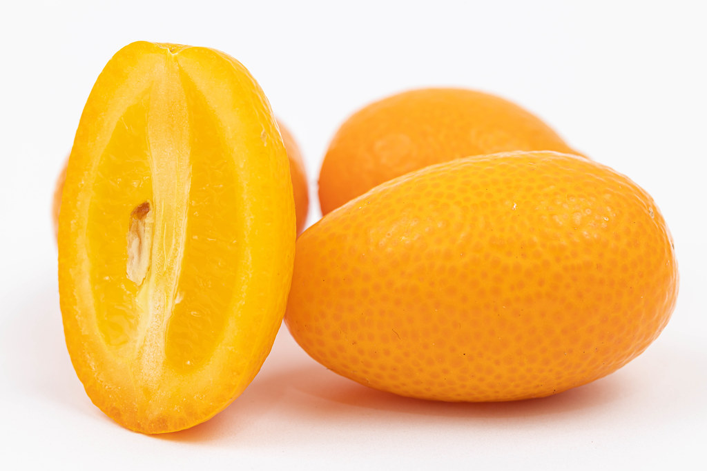 Sliced Kumquat above white background with copy space