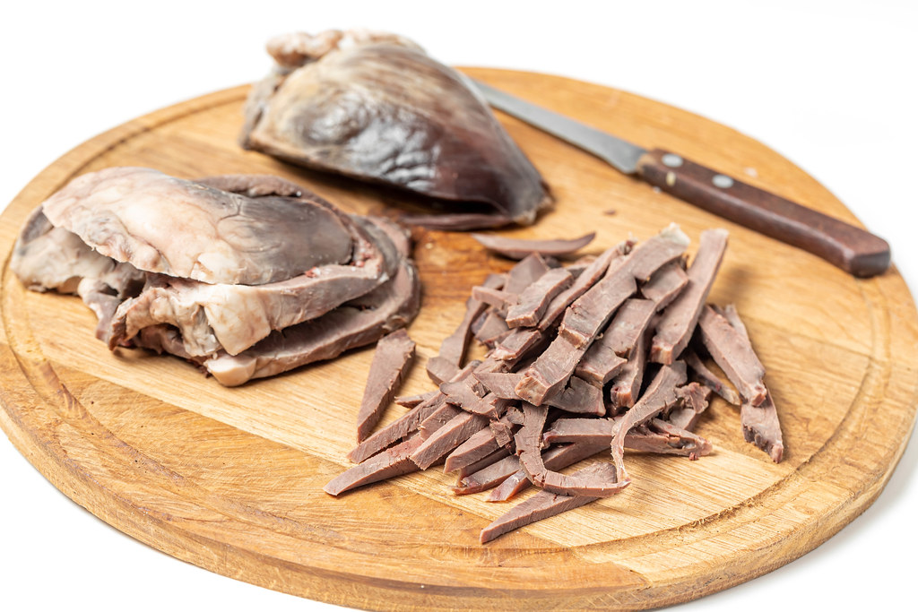 Sliced pieces cooked heart on a wooden kitchen board with a knife