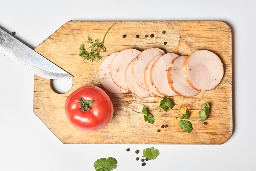 Sliced pieces of smoked chicken meat on wooden cutting board