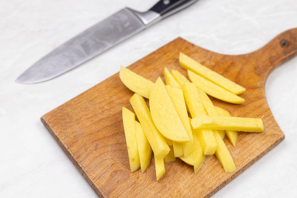 Sliced raw potatoes on the wooden cutting board