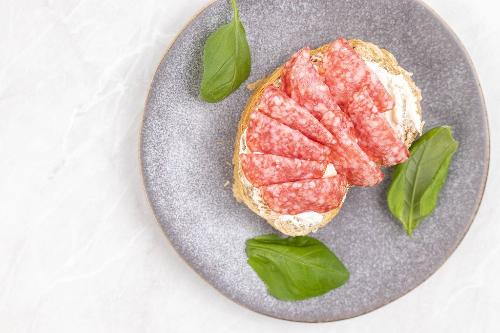 Sliced Sausage served on the bread with Basil leaves