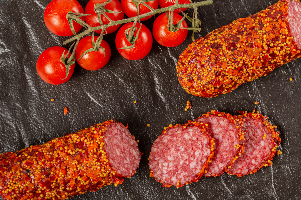 Sliced smoked sausage with spices and tomatoes on a dark background