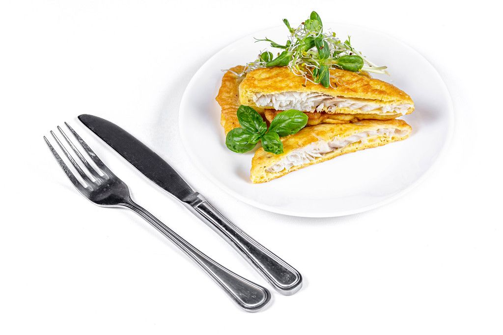 Slices fried fish in batter with fresh micro greens on a white background with a knife and fork