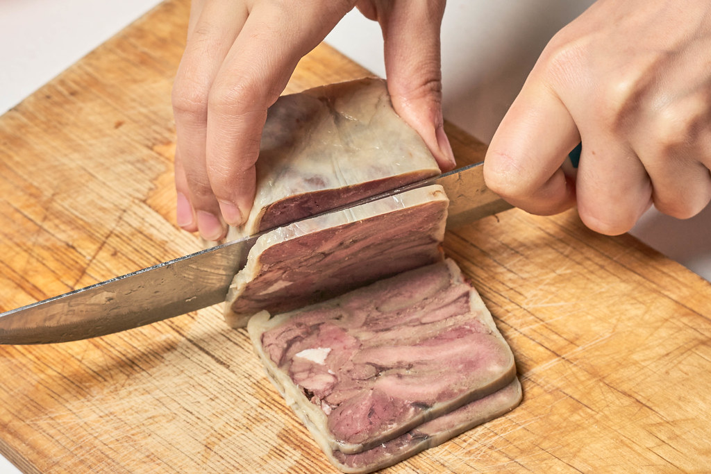 Slicing smoked meat product on cutting board