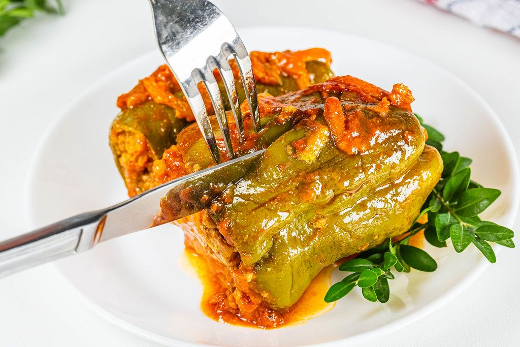 Slicing stuffed bell peppers, close-up