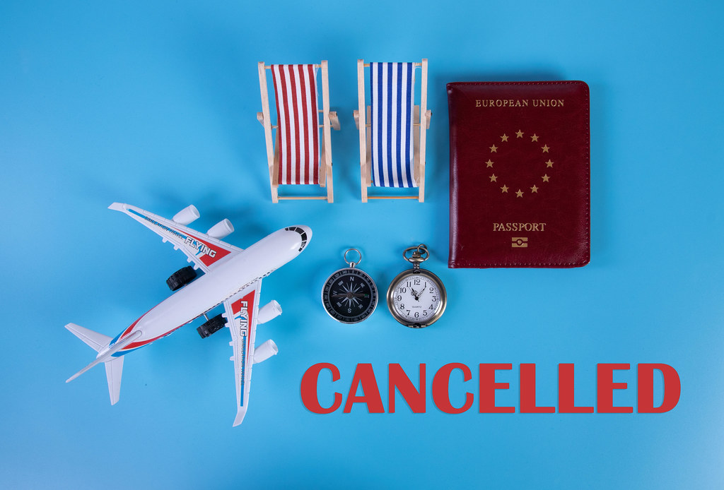 Small airplane, passport and beach chairs with Cancelled text on blue background
