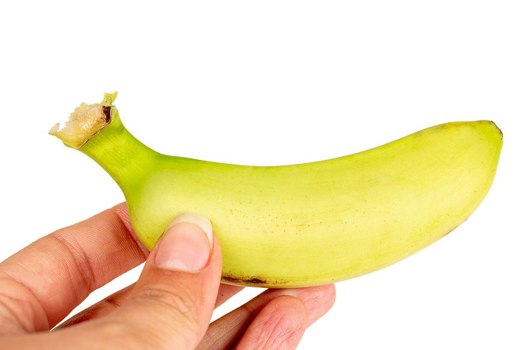 Small fresh banana in a female hand